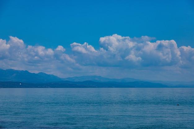 Zeegezicht wolken op de achtergrond van bergen en blauwe zee.