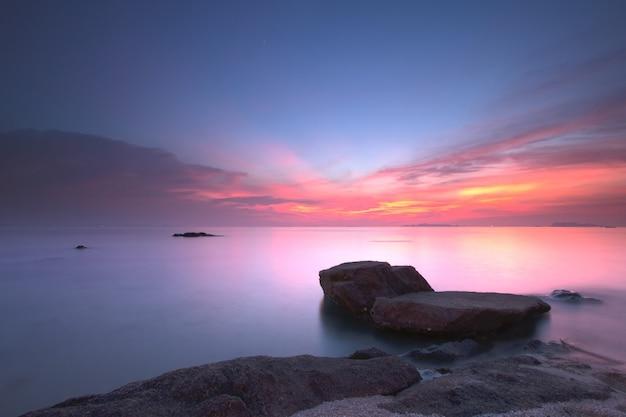 Zeegezichtzonsondergang met fantastisch rotsoppervlak en rode hemel, lange blootstellingstechniek
