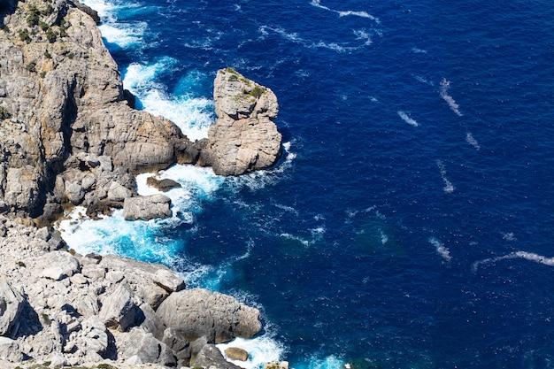 Zeegolf breekt op het landschap van strandrotsen. zeegolven beuken en spatten op rotsen