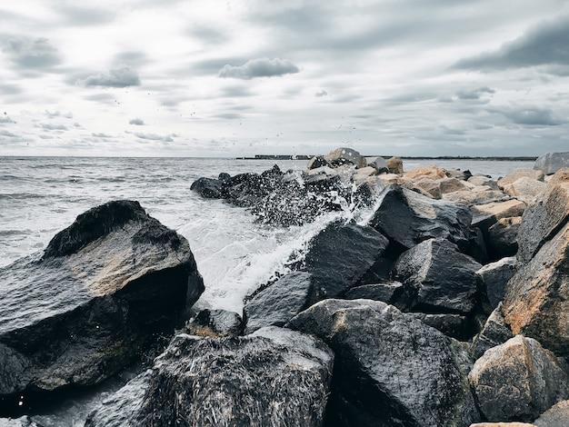 Zeegolven breken op rotsen met waterspatten