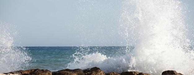Zeegolven die tegen de rotsen beuken