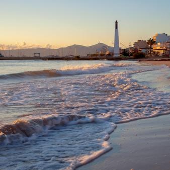 Zeegolven en zonsondergang op het strand van mallorca can picafort