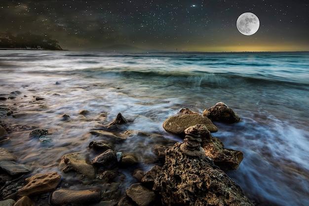 Zeegolven op het steenachtige strand 's nachts met een sterrenhemel en een volle maan