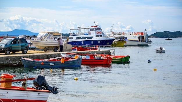 Zeehaven, meerdere afgemeerde boten op de egeïsche zee, een man haakte een boot aan de auto op een pier in ouranoupolis, griekenland