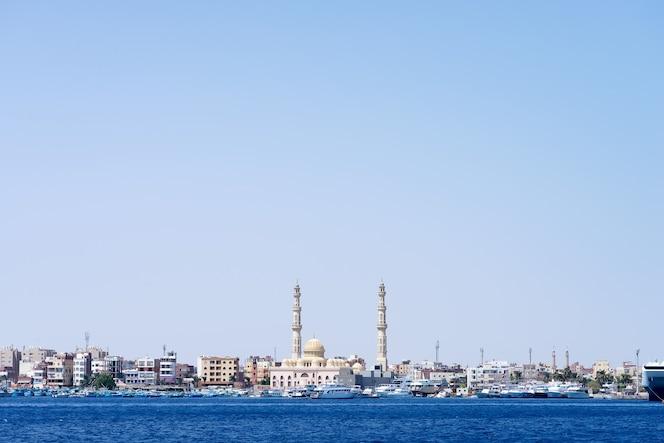 Zeehaven met stenen stadsdijk met geparkeerde speedboten en de moskee van Hurghada