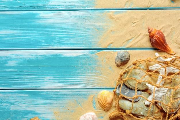 Zeekabel met veel verschillende zeeschelpen op het zeezand op een blauwe houten achtergrond in bovenaanzicht