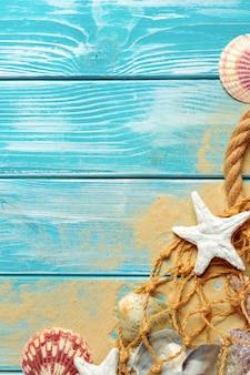 Zeekabel met veel verschillende zeeschelpen op het zeezand op een houten blauw. bovenaanzicht
