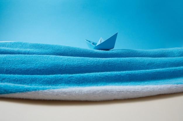 Zeekust gemaakt van badstof handdoek met papieren handwerkschip in de golven op een achtergrond van blauwe lucht en beige zand, plaats voor tekst.