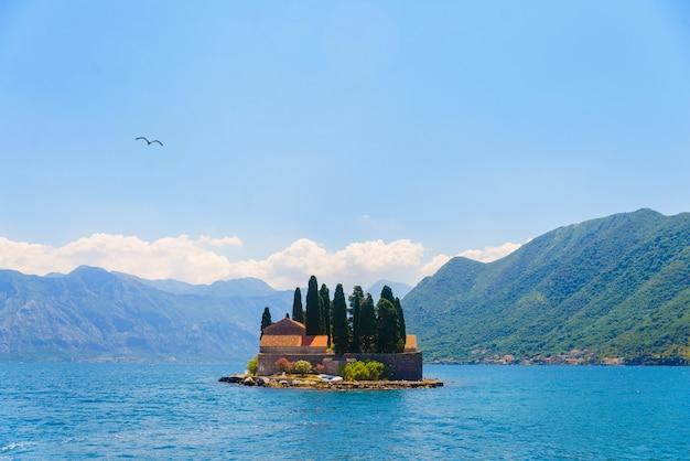 Zeemeeuw die over een eiland in de baai van boko kotor, montenegro vliegt.