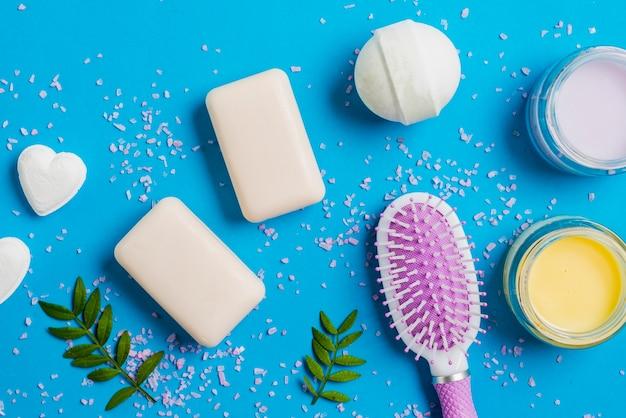 Zeep; bad bom; vochtinbrengende crème en haarborstel op blauwe achtergrond