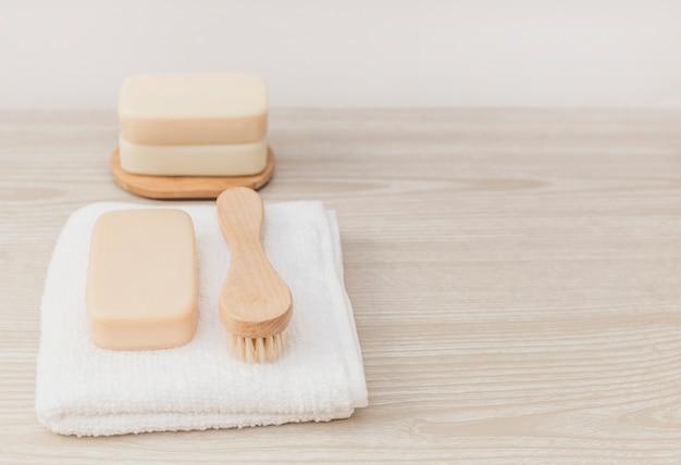 Zeep; borstel en handdoek op houten tafelblad