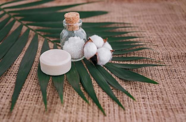 Zeep, zeezout in glazen fles en katoenbloem op palmblad