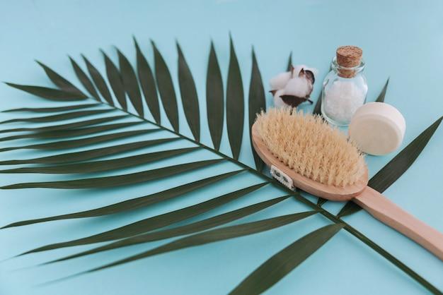Zeep, zeezout in glazen fles, natuurlijke borstel en katoenbloem op palmbladblauw