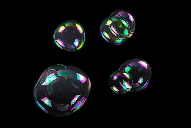 Zeepbellen die op een zwarte achtergrond worden geïsoleerd
