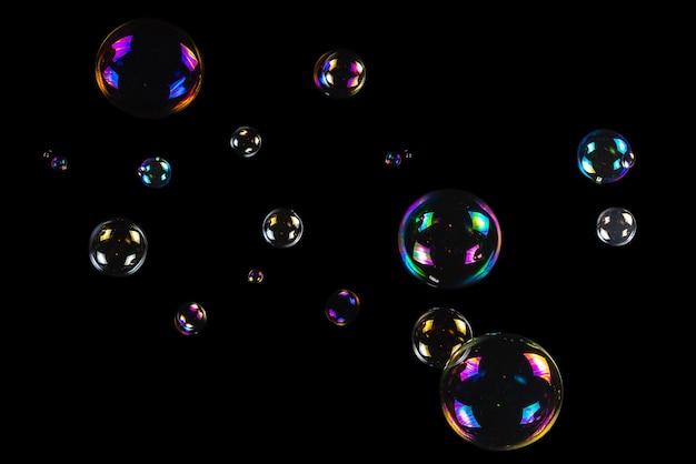 Zeepbellen geïsoleerd op een zwarte achtergrond. kopieer ruimte.