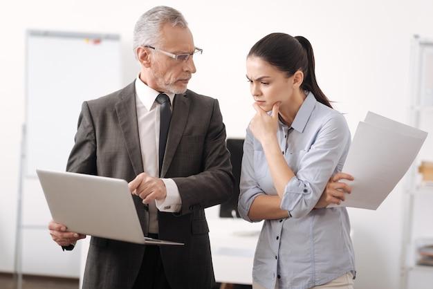 Zeer attente brunette haar voorhoofd rimpels houden papieren in rechterhand, kin aan te raken tijdens het kijken naar de computer