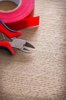 Zeer close-up elektrische kniptang en rol isolatietape op een houten bord