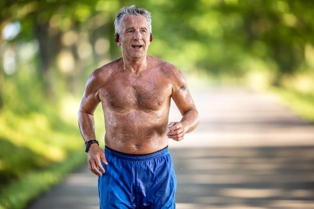 Zeer fitte man van in de 70 loopt alleen in zijn korte broek buiten in de natuur.