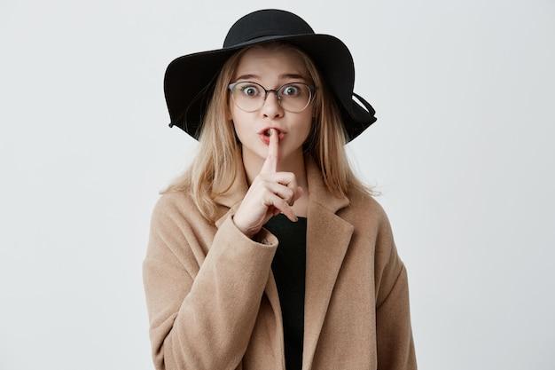 Zeer geheim. schattige blonde jonge vrouw met bril, jas en hoed, met afgeluisterde ogen die een vinger op haar lippen houdt, 'shh' zegt, vraagt om te zwijgen over haar grote geheim, kijkend naar de camera