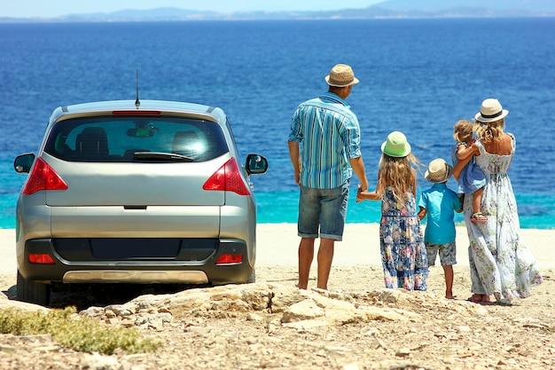 Zeer gelukkige familie met de auto aan zee