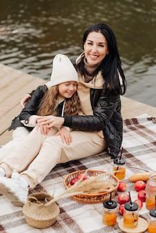 Zeer gelukkige familie op een herfstpicknick bij de herfstfotosessie van het meer