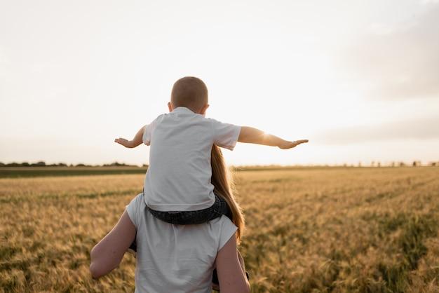 Zeer gelukkige familie van moeder en zoon die buiten plezier hebben bij zomerzonsondergang