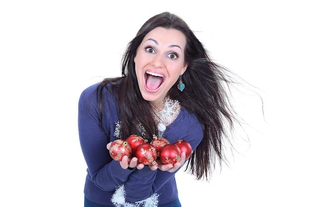 Zeer gelukkige jonge vrouw die kerstballen toont.
