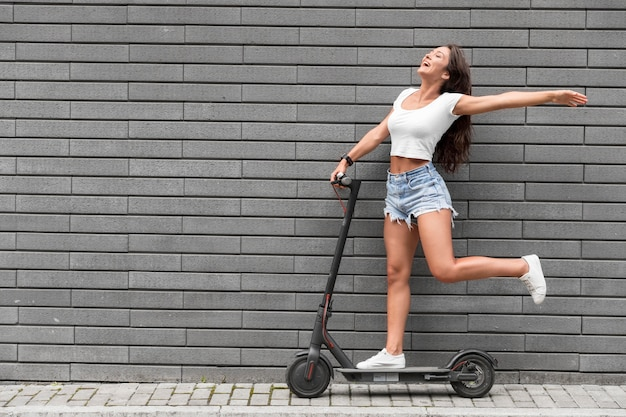 Zeer gelukkige vrouw die zich voordeed op elektrische scooter