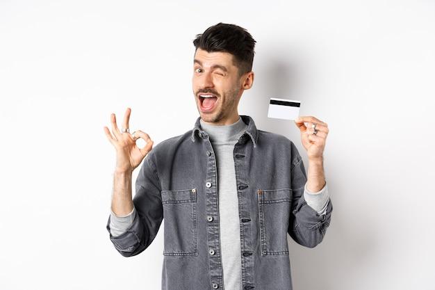 Zeer goed. glimlachende man met plastic creditcard die ok teken toont, glimlachend en tevreden knipoogt, raadt bank aan, die zich op witte achtergrond bevindt.
