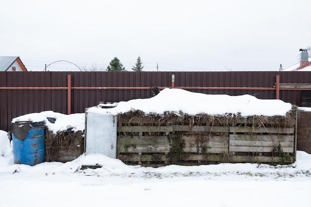 Zeer grote driedelige houten compostbak staande tuin in de winter op het platteland voor ecologische compostering van voedsel en tuinafval