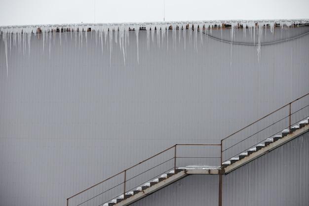 Zeer grote ijspegels hangen aan het dak.