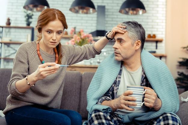 Zeer hoge temperatuur. aardige bezorgde vrouw die naar de elektronische thermometer kijkt terwijl ze zich zorgen maakt over haar man