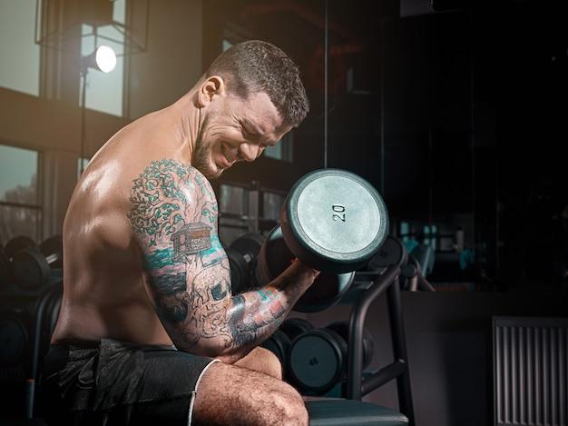 Zeer krachtige atletische kerelbodybuilder, voer oefening met domoren uit, in donkere gy,