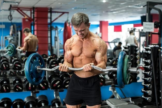 Zeer krachtige atletische man staande training in de sportschool