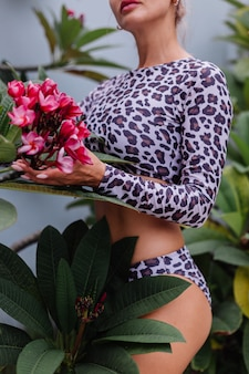 Zeer mooie blanke vrouw met perfect fit lichaam in luipaardzwempak met tropische mooie bloemen
