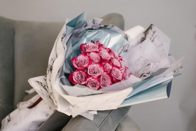 Zeer mooie bloemistvrouw die een mooi kleurrijk bloeiend boeket van bloemen op een grijze muurachtergrond houdt.