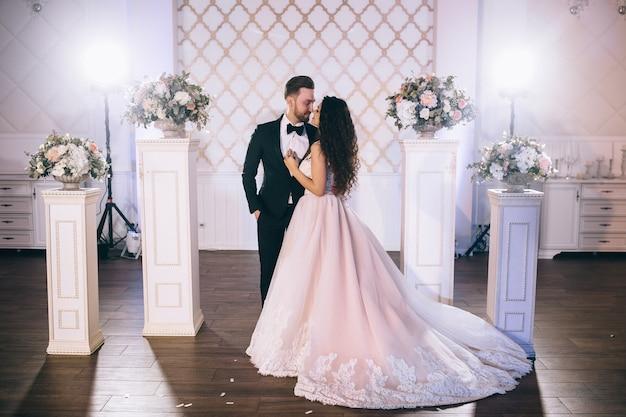 Zeer mooie en gelukkige pasgetrouwden staan bij een prachtig versierde huwelijksboog tijdens hun huwelijksceremonie