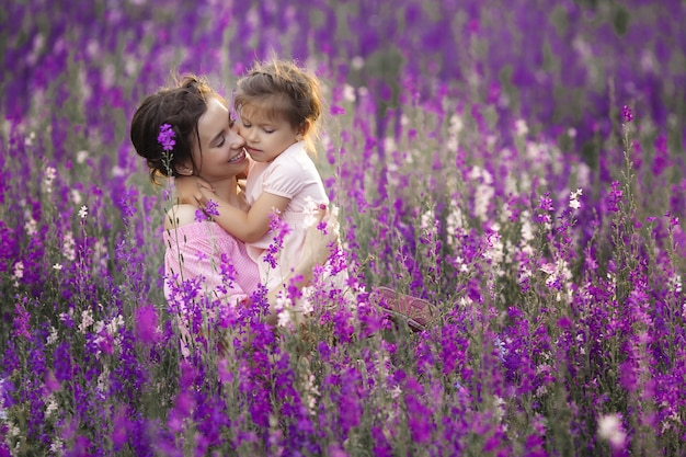 Zeer mooie foto van jonge moeder en kind in het bloemenveld