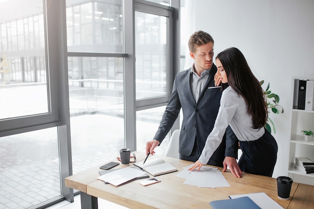 Zeer mooie jonge brunette staan dicht bij haar baas en kijk naar beneden. ze houdt haar hand op zijn schouder.