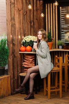 Zeer mooie jonge vrouw, zit in cafe en drink koffie of thee met croissant, vooraanzicht van de straat