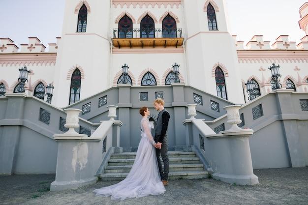 Zeer mooie roodharige jonge net getrouwd gelukkig paar kussen in de zonsondergang buitenshuis