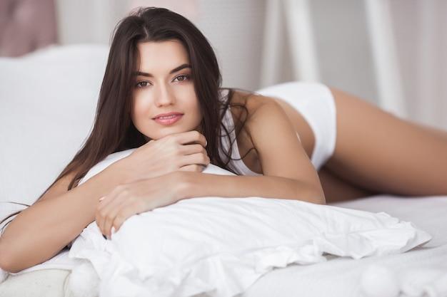 Zeer mooie vrouw in het bed. portret van jonge aantrekkelijke dame in de slaapkamer