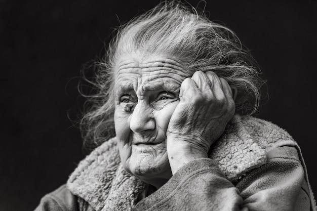 Zeer oude en moe gerimpelde vrouw buitenshuis