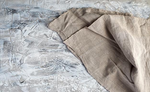 Zeer oude grijze uitstekende keukenhanddoek op grijze cementachtergrond