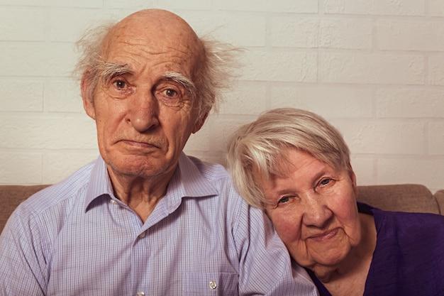 Zeer oude oma en opa knuffelen op de bank liefde op hoge leeftijd vrouw legt haar hoofd op de schouder van echtgenoot ouderen