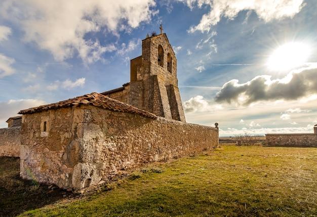 Zeer oude stenen kerk in het midden van het veld met blauwe lucht, wolken en zon. landelijke omgeving. segovia