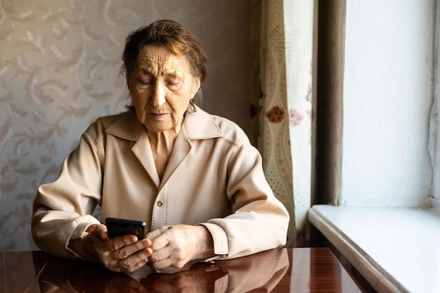 Zeer oude vrouw gebruikt een smartphone in huis.