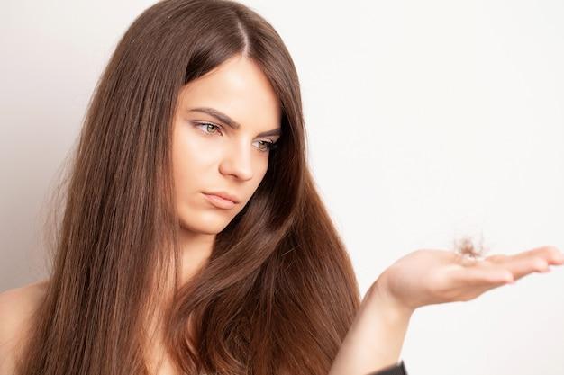 Zeer overstuur jonge vrouw heeft een probleem met haaruitval