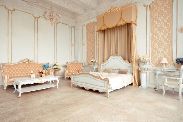 Zeer rijk interieur van het appartement met gouden decoraties aan de muren in barokstijl en luxe meubels met goudverf.