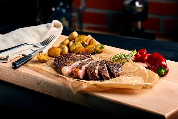 Zeer sappige ribeye-steak van marmerrundvlees op een houten tafel met baby-aardappelen